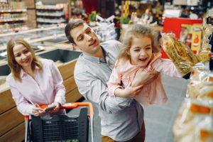 A happy family shops for affordable groceries together.