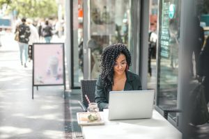 A woman enjoys free wifi on her laptop outside.