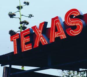 A neon Texas sign at a cheap travel destination.