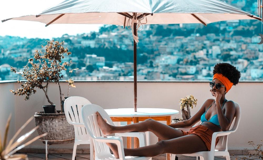 A woman relaxes under an umbrella.